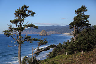 Photo of Canon Beach, OR taken from a hill overlooking the city looking North. Haystack Rock is framed between two evergreen trees.